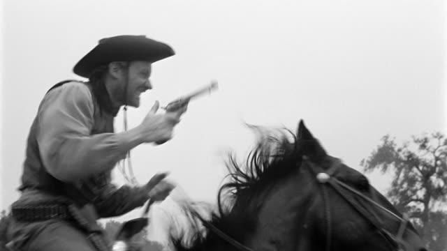 black and white 1940s low angle medium shot tracking shot cowboy riding horse and firing pistol - cowboy stock-videos und b-roll-filmmaterial