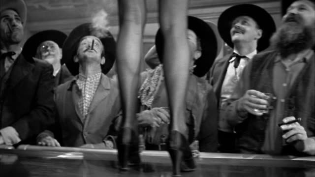 black and white 1940s medium shot cowboys and women gawking at showgirl's legs as she walks along the bar - showgirl stock videos and b-roll footage