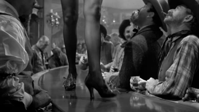 black and white 1940s medium shot cowboys gawking at showgirl's legs as she walks along bar - showgirl stock videos and b-roll footage