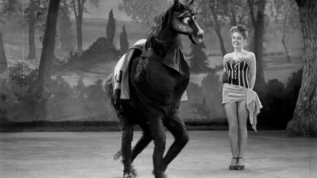 Black and white 1940s wide shot dancer smiling and fake horse Pansy (Andy + Florence Mayo) doing kick dance on stage