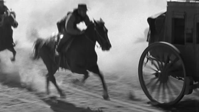 black and white 1940s wide shot tracking shot cowboys on horseback chasing runaway stagecoach / jumping from one horse to another - cowboy stock-videos und b-roll-filmmaterial