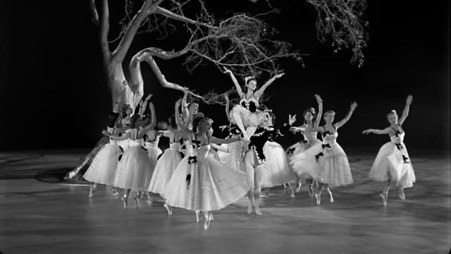stockvideo's en b-roll-footage met black and white 1940s wide shot women performing ballet dance with tree on set in background / man holding ballerina up - balletdanser