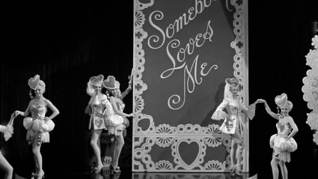 "black and white 1940s wide shot zoom out dancers standing in front of ""somebody loves me"" sign / revealing light-up heart - theatrical performance stock videos & royalty-free footage"