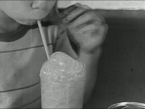 Black and white 1942 close up boy blowing bubbles in glass through straw / AUDIO