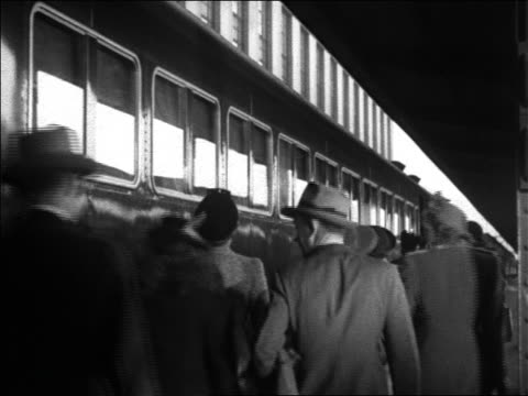 black and white 1942 rear view people walking beside parked train at station / conductor stands by train /audio - prelinger archive stock videos and b-roll footage