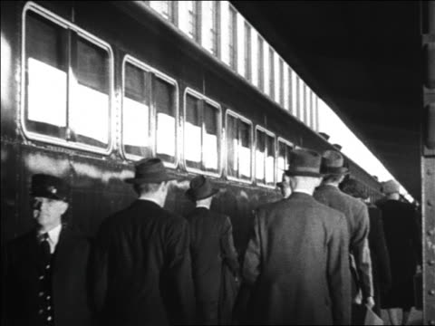black and white 1942 rear view people walking beside parked train at station / conductor stands near train audio - passeggero video stock e b–roll