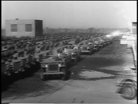 black and white 1943 high angle pan men driving military jeeps into warehouse / industrial /audio - ford motor company stock videos and b-roll footage