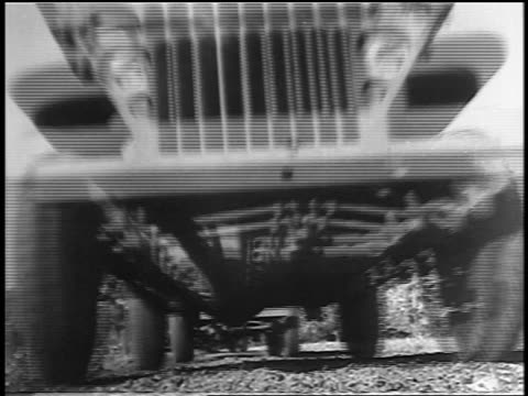 black and white 1943 low angle close up military jeeps driving over camera / industrial /audio - ford motor company stock videos and b-roll footage