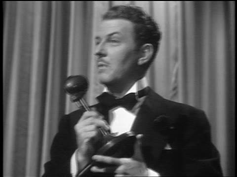 vidéos et rushes de black and white 1943 man in tuxedo talking into microphone then looking to side / feature /audio - smoking
