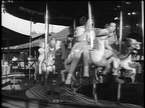 Black and white 1944 adults and children riding horses on carousel past camera / documentary