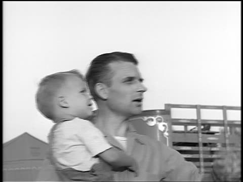 Black and white 1944 close up profile man holding small boy / they talk and point up / documentary