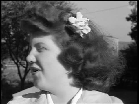 vídeos y material grabado en eventos de stock de black and white 1944 close up teen girl with flower in hair talks to side then turns to drink from glass / documentary - sólo chicas adolescentes