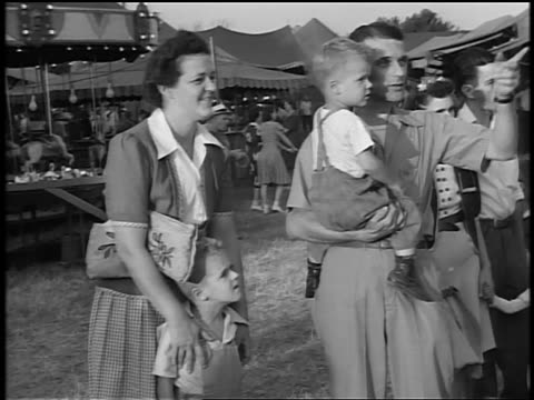 vídeos de stock e filmes b-roll de black and white 1944 couple with 2 boys at fair / man holds 1 boy and points, woman w/ hands on other's shoulders - 1944