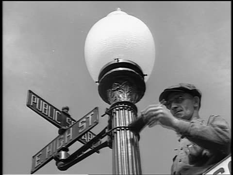 vídeos de stock, filmes e b-roll de black and white 1944 low angle man painting street light post with street signs / documentary - placa de nome de rua