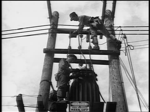 black and white 1944 low angle two repairmen working on telephone lines on pole / documentary - linea telefonica video stock e b–roll
