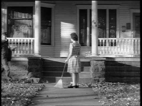 black and white 1944 mailman gives mail to woman sweeping sidewalk in front of house / documentary - stay at home mother stock videos & royalty-free footage