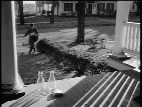 vidéos et rushes de black and white 1944 mailman walks on sidewalk and puts mail on porch of house / documentary - facteur
