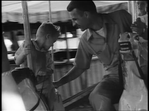 Black and white 1944 man and young boy riding horses on carousel / documentary