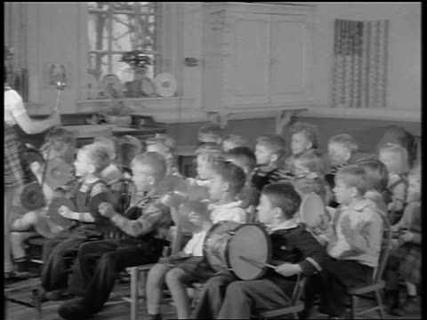 black and white 1944 pan children playing musical instruments, girl conducting band, teacher playing piano - 女性教師点の映像素材/bロール