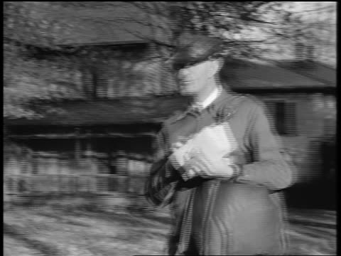 black and white 1944 pan mailman walking past suburban houses / documentary - postal worker stock videos & royalty-free footage