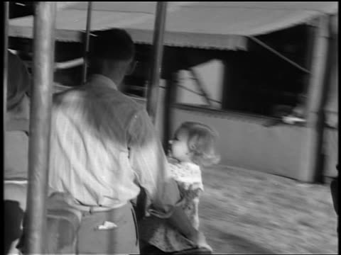 black and white 1944 rear view man holding small girl on horse on carousel / documentary - carousel horse stock videos and b-roll footage