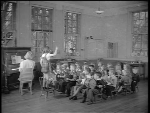 black and white 1944 teacher plays piano while young girl conducts children in band in classroom / documentary - primary school child stock videos & royalty-free footage