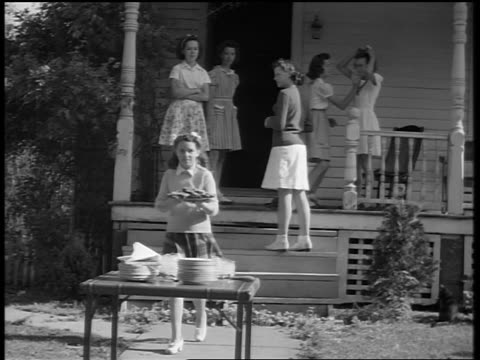 vídeos de stock e filmes b-roll de black and white 1944 teen girl carries plate of food from porch to table on sidewalk / documentary - só meninas adolescentes