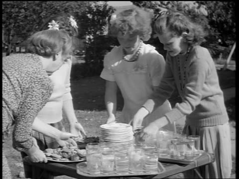 black and white 1944 woman puts plate of cookies on table with glassware and dishes / teen girls arrange table - biscuit stock videos & royalty-free footage