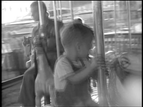 black and white 1944 young boy riding horse on carousel / documentary - carousel horse stock videos and b-roll footage