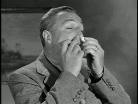 Black and white 1945 close up man inhaling nasal spray into both nostrils / AUDIO
