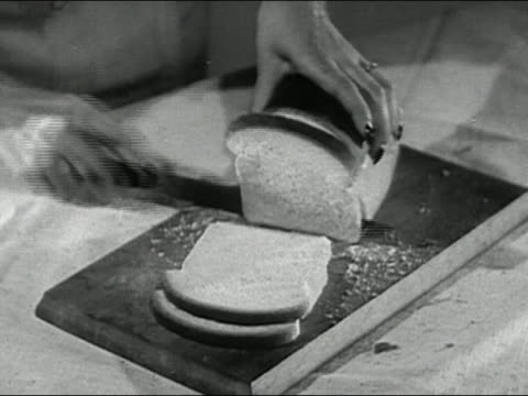 black and white 1946 high angle close up woman's hands slicing white bread on a breadboard / audio - bread stock videos & royalty-free footage