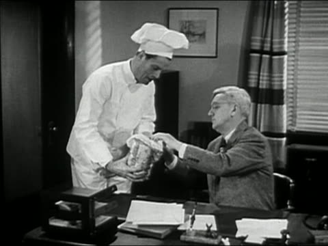 black and white 1946 medium shot baker showing businessman loaf of sliced bread in office - white bread stock videos and b-roll footage