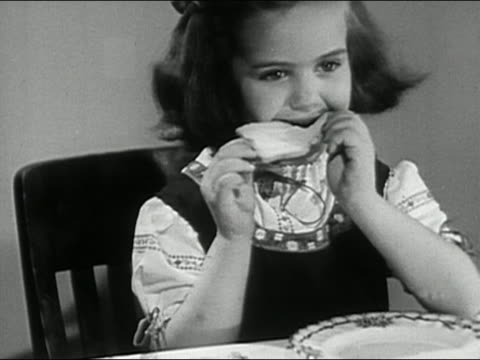 black and white 1946 medium shot girl eating slice of white bread / audio - white bread stock videos and b-roll footage