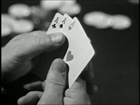 Black and white 1948 close up hands holding four ace cards