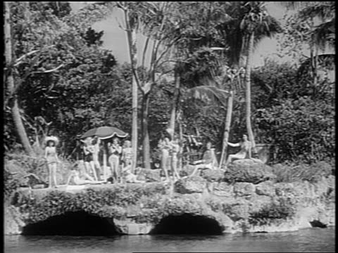 black and white 1948 wide shot women in swimsuits relax outdoors and play with beach ball / coral gables, fl / newsreel - hawaiian culture stock videos & royalty-free footage