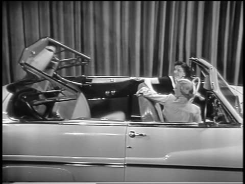 black and white 1949 2 women sitting in mercury convertible in showroom as soft top goes up / industrial - collector's car stock videos and b-roll footage