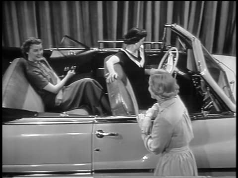 black and white 1949 high angle 2 women sitting in mercury convertible in showroom as power windows go up / indust. - 1949 stock-videos und b-roll-filmmaterial