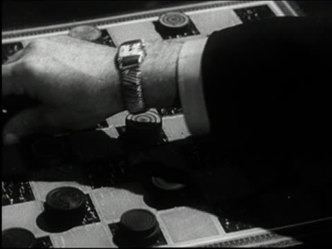 Black and white 1950s close up hands playing game of checkers / AUDIO