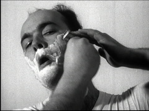 black and white 1950s close up man shaving face w/razor and shaving cream / tv commercial / audio - raso video stock e b–roll