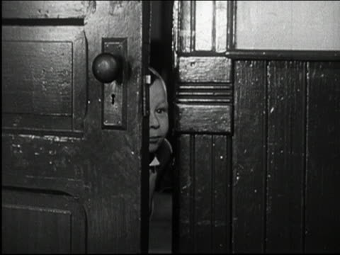 Black and white 1950s close up young boy opening door and peeking into room /  AUDIO