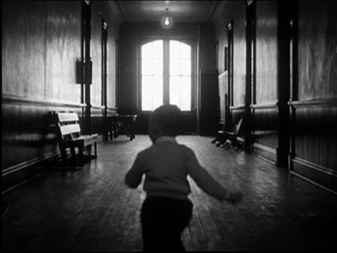 vidéos et rushes de black and white 1950s long shot young boy running down dark hall and into doorway / audio - espièglerie