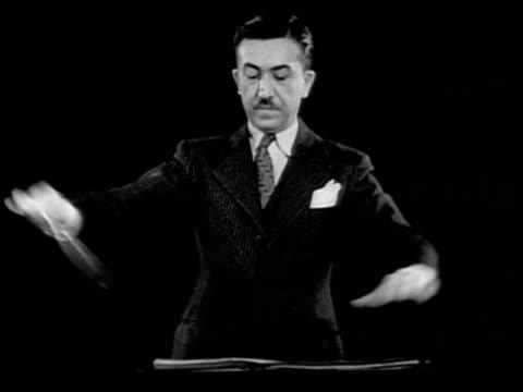 stockvideo's en b-roll-footage met black and white 1950s medium shot conductor michael ficocelli at podium waving baton while conducting orchestra / audio - menselijke arm