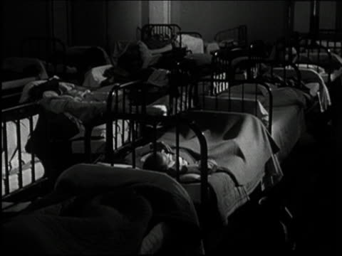black and white 1950s medium shot male firefighters lying in beds in firehouse wake up suddenly to siren / audio - ヘッドボード点の映像素材/bロール