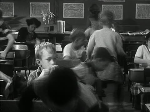 black and white 1950s medium shot zoom in children leaving classroom / young boy biting nails and getting up slowly / audio - schoolboy stock videos & royalty-free footage