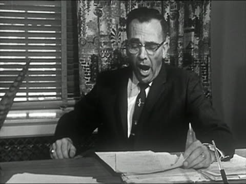 black and white 1963 medium shot business man yawning at his desk / audio - yawning stock videos & royalty-free footage
