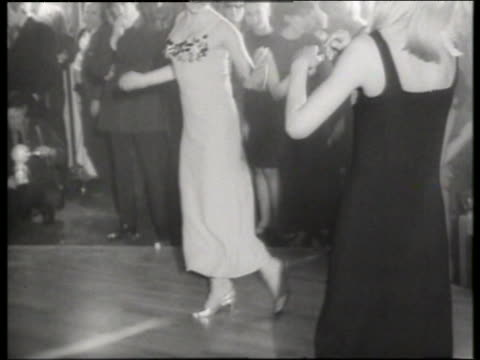 Black and white 1965 2 fashion models dancing for audience / tilt down to feet / Fashion show / AUDIO