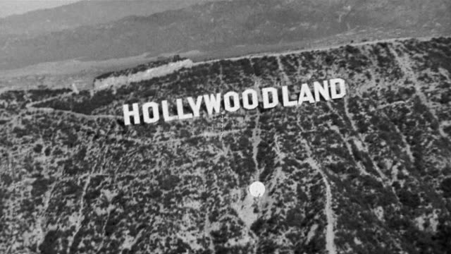 "1930 black and white aerial view of ""hollywoodland"" sign / los angeles, california - hollywood los angeles video stock e b–roll"