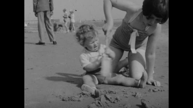 black and white archive home movie footage of british holidaymakers on the beach in the seaside resort of sandown on the isle of wight circa 1940s - swimwear stock videos & royalty-free footage