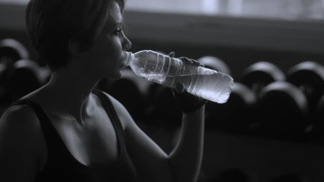 白黒: 運動後に水を飲むアスリート女性 - 中年点の映像素材/bロール