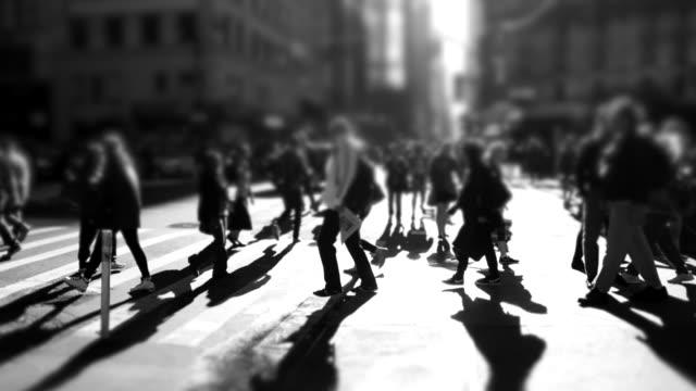 vídeos de stock, filmes e b-roll de black and white background of people crossing street in the city - mala de rodinhas